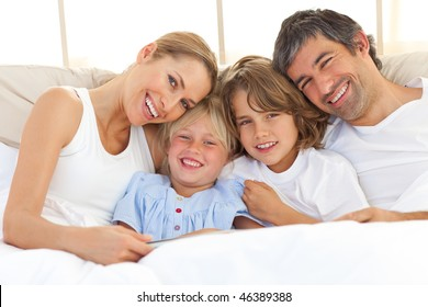 Happy family reading a book  lying in bed
