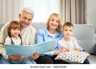 Happy family reading book on couch
