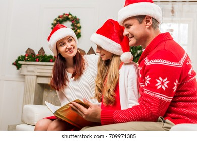 happy family reading book together on christmas