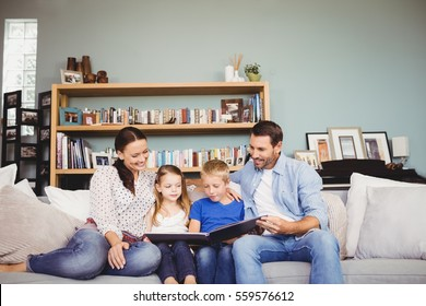 Happy family reading book while sitting on sofa at home