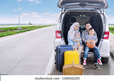 Happy family ready for a road trip while looking at the camera and sitting together in the car trunk. Shot on the highway