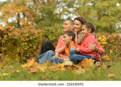 Happy family relaxing in autumn park together