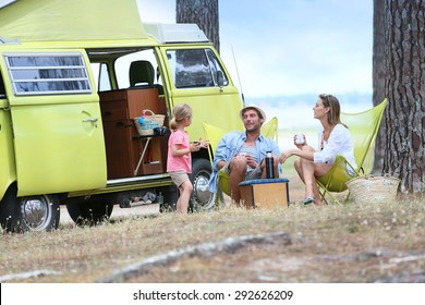 happy family relaxing by camper van in summer