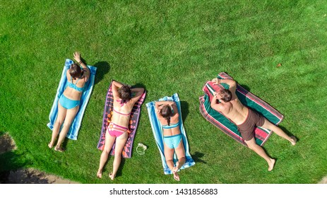 Happy family relaxing by swimming pool, aerial drone view from above of parents and kids have fun on vacation, family weekend on resort