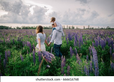 Happy family relaxing and having fun in beautiful lupine field on cloudy day
