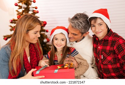 Happy family relaxing at home with Christmas presents.