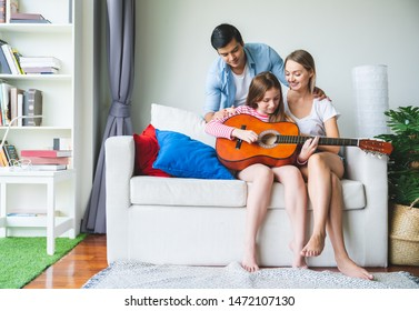 Happy family relaxing at home on sofa while playing guitar and singing songs having dad Mom and children are happiness. Spending quality leisure time and Creating activities to strengthen skills.