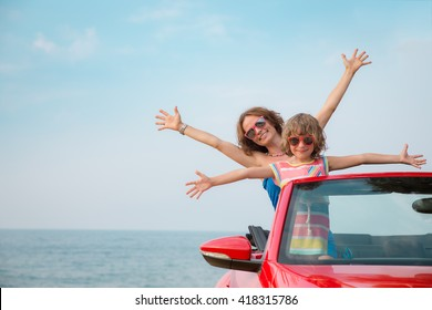 Happy family relaxing on the beach. Woman and child having fun in red cabriolet against blue sky background. Summer vacation and travel concept