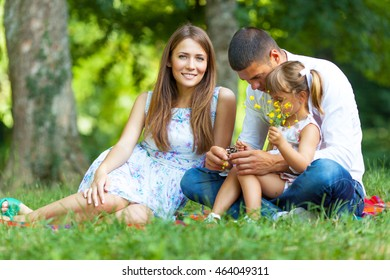 Happy family relaxing at the park on beautiful summer day