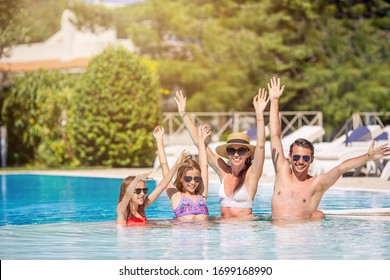 Happy family relaxing in swimming pool