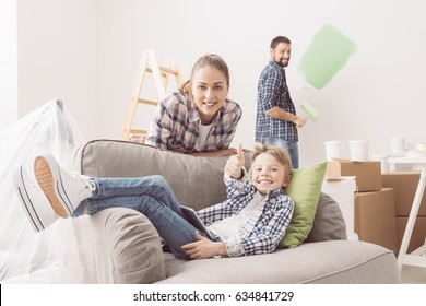 Happy family renovating their home, they are connecting with a tablet and painting the room, the boy is giving a thumbs up