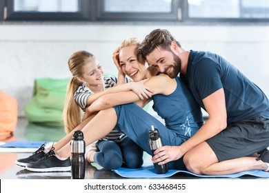 Happy family resting after workout at gym