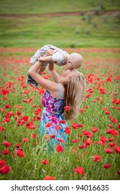 Happy family resting in the field with poppies