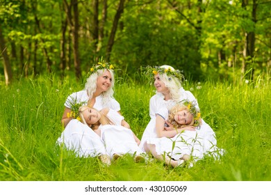Happy family resting on the nature in the summer. Mom and daughter with wreath in the flowers in the park. Girls sitting in the park on the grass
