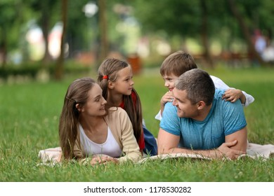 Happy family resting on plaid in park