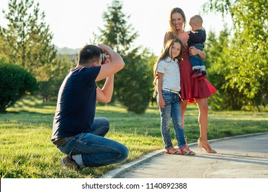 happy family is resting in the park in summer . beautiful mother , handsome father with a little baby boy and cute daughter photographed on camera . family photo shoot male photographer