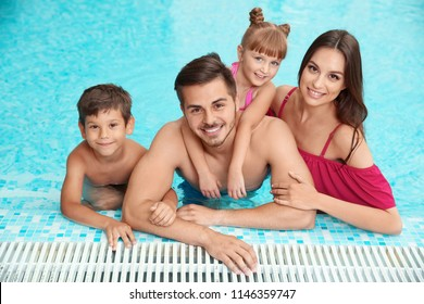 Happy family resting in swimming pool with refreshing water
