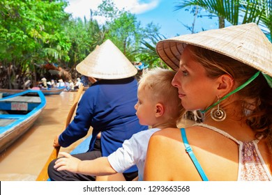 Happy family ride on traditional Vietnamese boat by yellow brown water in canal. Mekong river delta - popular travel destination for day tour during vacation in Saigon ( Ho Chi Minh ) city, Vietnam.