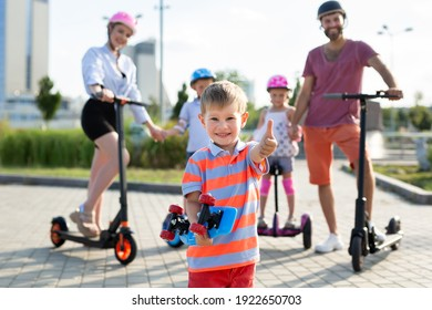 Happy family rides electric scooters and gyroscuters in the park, in the foreground a small boy holds a skate in his hands and gives a thumbs up