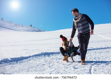 the happy family rides the sledge in the winter wood, cheerful winter entertainments