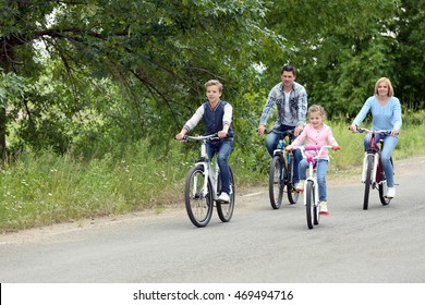 Happy family riding bikes on road