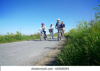 Happy family riding bikes on week-end in countryside