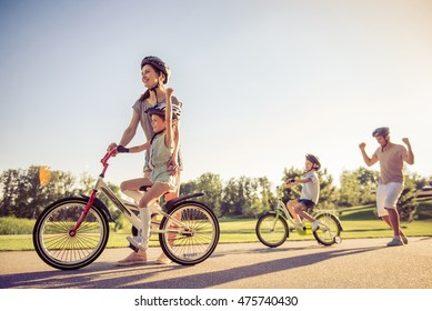 Happy family is riding bikes outdoors and smiling. Parents are teaching their children. Dad is holding fists