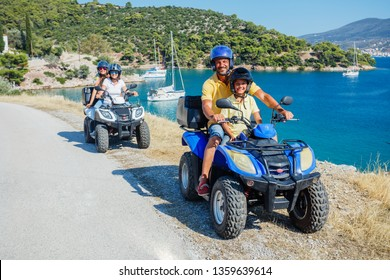 Happy family riding and looking quad bike on Greece island. Cute boy and his father on quadricycle. Motor cross sports on Greece island. Family summer vacation activity.