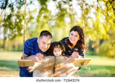 happy family riding on a swing in the evening park