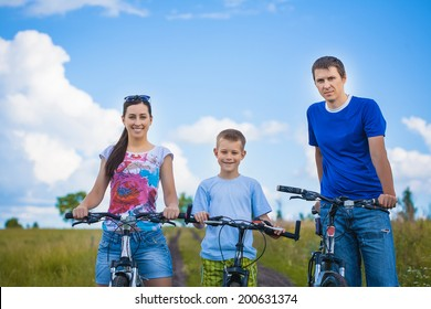 Happy family are riding in the summer field