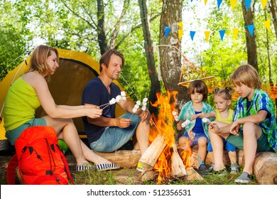 Happy family roasting marshmallow over the fire