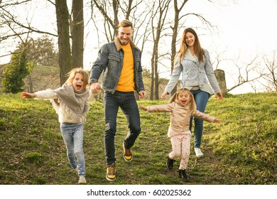 Happy family run through the park.