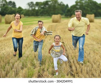 Happy family  run in wheat field in sunny day
