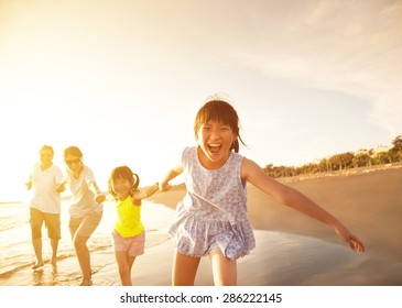 happy family running on the beach