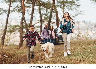 Happy family runs and having fun with their dog near modern car outdoors in forest.