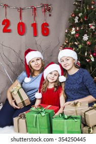 Happy family in santa claus hats next new year number 2016 and Christmas tree with presents