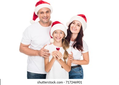 Happy family in Santa hats with heart shaped confetti, isolated on white
