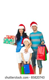 Happy family with Santa hats holding Christmas presents isolated on white background