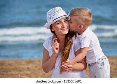 Happy family at sea summer. Little boy son hugs and kisses mother. Child loves mom. Portrait young woman in hat together with cute kid having rest on beach. concept of holiday, vacation.