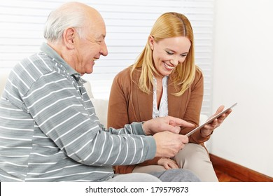 Happy family with senior citizen using a tablet computer