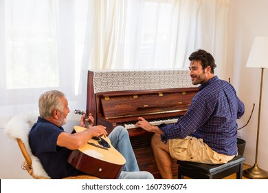 Happy family, Senior Father playing guitar and Adult Son playing Piano at home. Family sing a song together at home.
