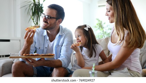 Happy family sharing pizza together at home