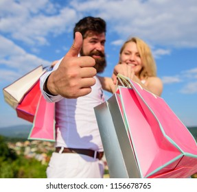 Happy family shoppers. Man with beard shows thumb up gesture. Couple in love recommend shopping summer sale discount season. Couple with shopping bags cuddle blue sky background. Advice to buy now.
