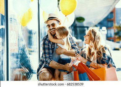 Happy family with shopping bags and ballons walking on street.