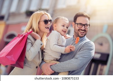 Happy family with shopping bags in the city.
