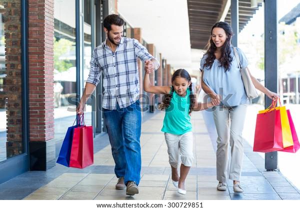 Familia feliz con bolsas de compras en el centro comercial