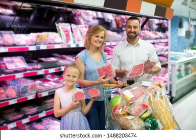 Happy family shopping various fresh red meat in supermarket