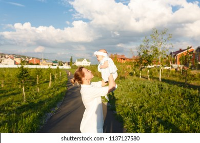Happy family shot. Beautiful picture of ypung attractive mommy holds toddler upstairs, has hice mood, rejoices at motherhood on beauty sky blue background with clouds and green city park outdoor