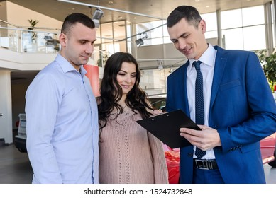 Happy family signing contract with dealer in salon