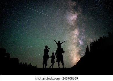 Happy family silhouette with Milky Way and beautiful night sky full of stars in background